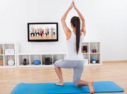 девушка делает гимнастику перед телевизором