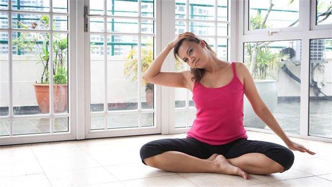 девушка выполняет упражнение для шеи дома