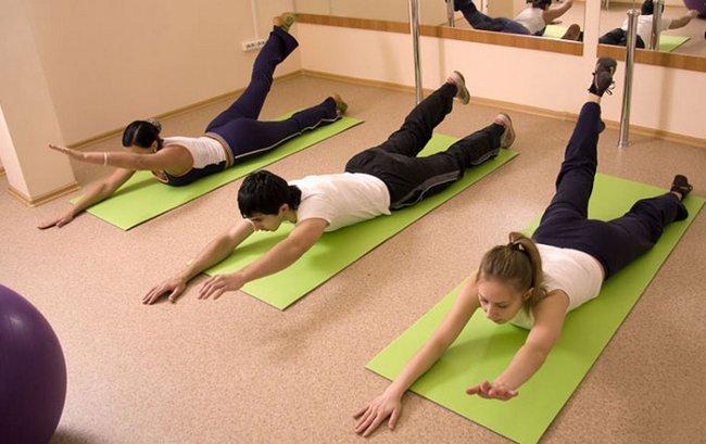 выполнение упражнения для спины на гимнастических ковриках